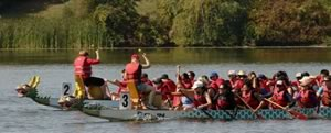 People in 2 dragon boats on the water