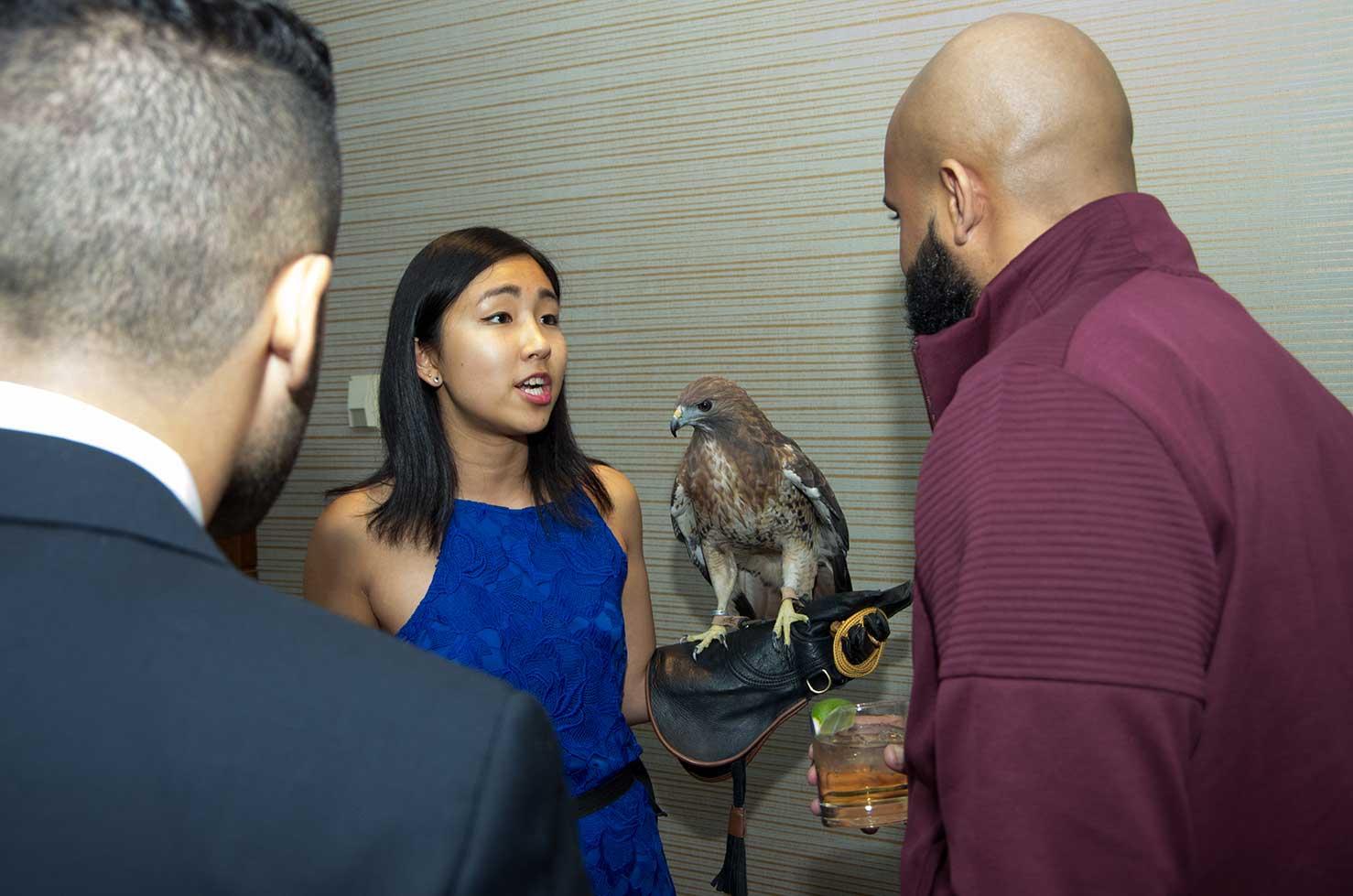 A woman holding a raptor bird