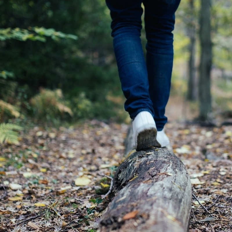 young woman balancing on log in forest