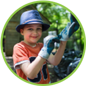 young boy wearing gardening gloves