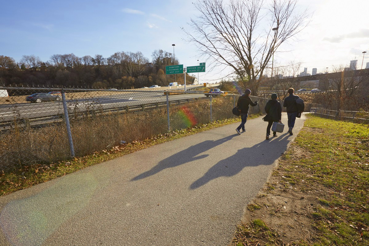a trio of young people walk the Don Trail in late afternoon on an autumn day