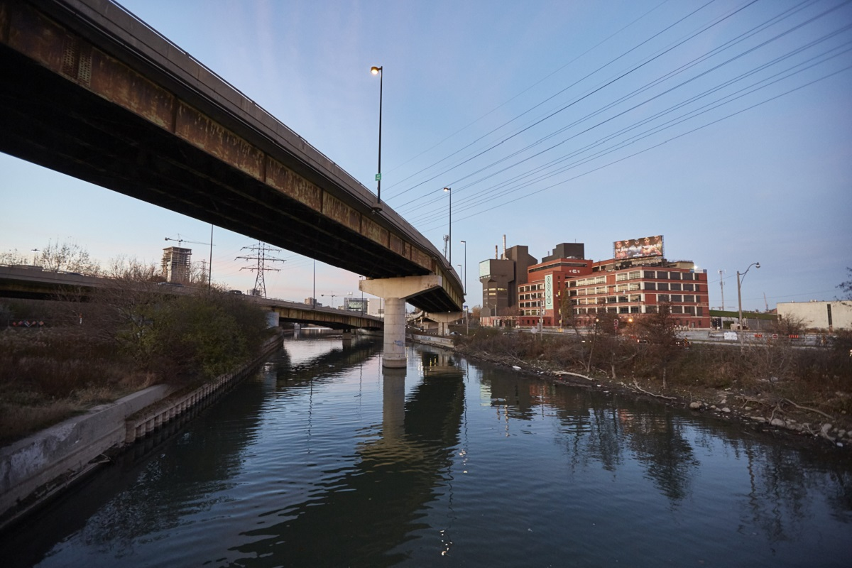 an industrial building and overpass are reflected in the still waters of the Don River
